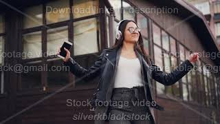 Slow motion of joyful girl student listening to music with headphones and dancing in the street in