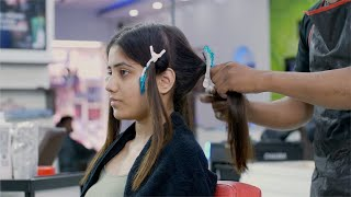 Pretty Indian girl getting a beautiful haircut by a hairstylist in a unisex salon