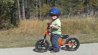 Big brother shows Strider running bike to little brother