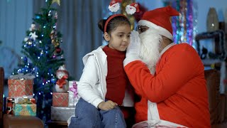 Smiling Indian girl sharing her secrets with Santa Claus while sitting on his lap - festive scene