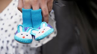 Closeup shot of hands with a pair of cute blue socks for a newborn baby in India