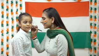 Indian woman painting the face of a little girl in Tricolors of a national flag - Independence Day / Republic Day concept