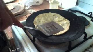 Making Chapati (indian Flat Bread). Toasting Dough On Flat Metal Pan