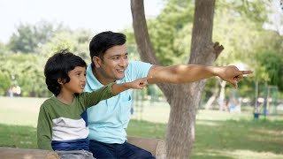 A handsome young man spending a beautiful summer day with his six-year-old kid in park in India