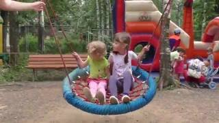 Дети катаются с горки, качаются на качелях на детской площадке в парке Космонавтов Ижевска.
