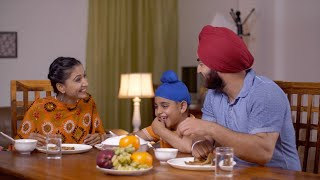 Happy nuclear Sikh family including a small child having dinner together at the table - family concept