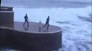 Guys jumping into huge waves