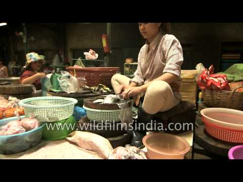 Woman cuts and fillets fish in a Cambodia market