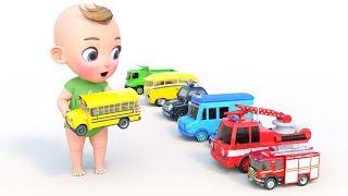 Un niño pequeño se juega con coches de juguete. Camión de bomberos, autobús escolar y ambulancia
