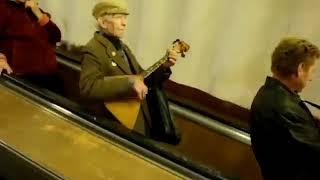 Дед играет в метро на балалайке.