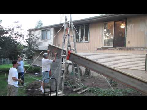 Using a pulley system to hoist a big steel beam for a sunroom