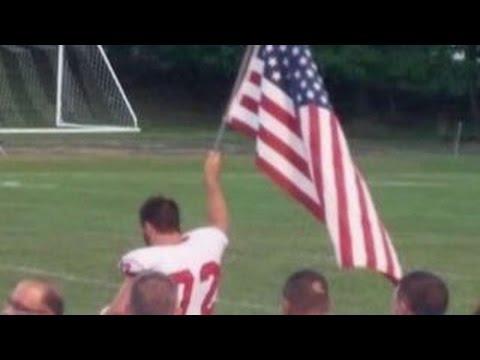 High School Football Player Raises American Flag At Game