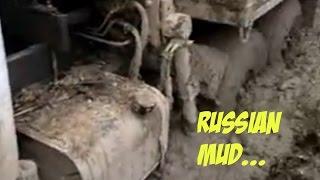 Трактор ДТ-75 тащит КрАЗ по грязи в делянке