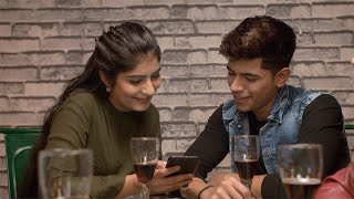 Cute Indian couple enjoying and having drinks together at a luxury lounge - leisure concept