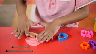 Closeup shot of a kid rolling a clay dough