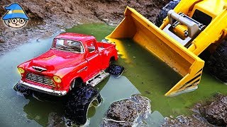 The monster truck is in a puddle of water. Construction vehicle bulldozer toy.