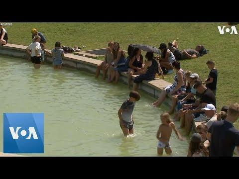 France Tourists Escape Heat In Eiffel Tower Fountains