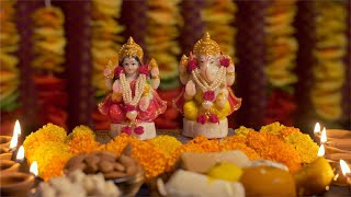 Diwali puja preparations with idols of goddess Lakshmi and Ganesha, a plate of sweets, diyas and dry fruits