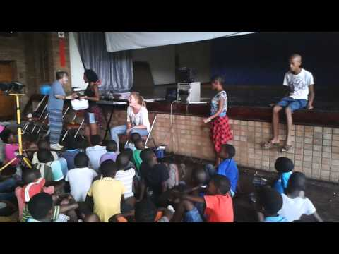 Soccer coach watches children sing at UBUNTU Community Hall