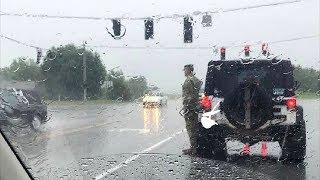 Солдат вышел из своего автомобиля, несмотря на дождь, и вытянулся в струнку отдавая честь