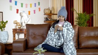 Beautiful young female drinking hot chocolate in a wrapped blanket and warm hat