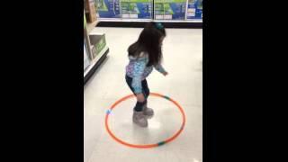 Niña que intenta bailar el hula hop