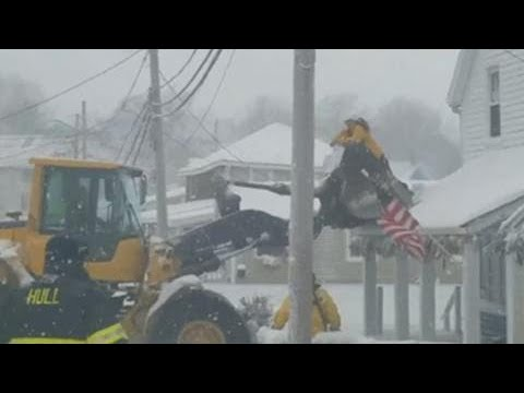 Loader rescues people trapped by frozen floodwaters in Hull, Massachusetts
