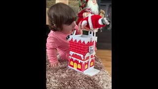 Little Girl Fascinated With Her New Moving Santa Toy