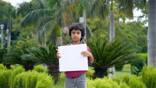 Small Indian child showing a white placard or a banner in a park - copy space concept
