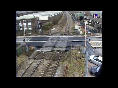 Driver swerves around railway barriers at level crossing