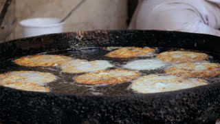 Closeup shot of hot cooking oil deep-frying delicious snacks - street food concept