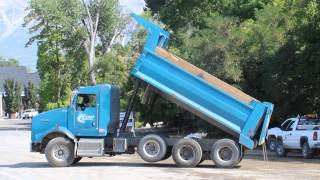Blue Kenworth Dump Truck slowly dumping his load of new dirt