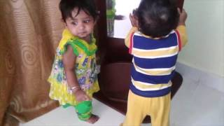 Twin babies fighting for mirror to see themselves in  the mirror