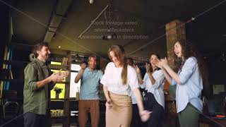 Company employees are dancing at corporate party in modern loft style office, attractive young men