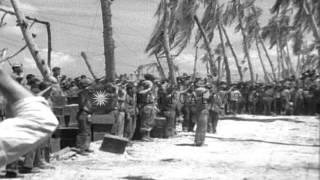 Marines salute the American flag-raising at Tarawa Island, Pacific Ocean. HD Stock Footage