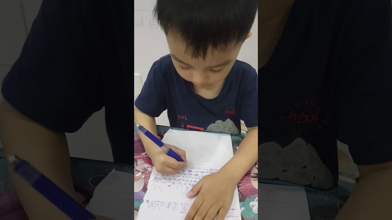 Bé trai ngồi cầm viết vẽ bậy giống như đang ngồi học.