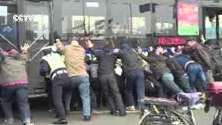 Crowd lifts bus to save trapped man