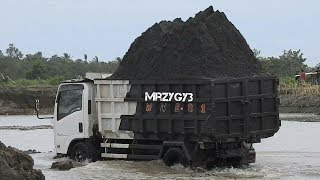 Overloaded Dump Truck On The River By Kobelco SK200-10 Keihatsu 921C Excavator
