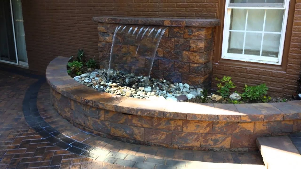 Outdoor living space with waterfall and firepit; by Corad ...