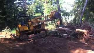 450 john deere loader pushing over a tree