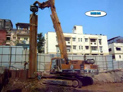 Sheet Pile Driving By Excavator Mounted Vibro Sinker At