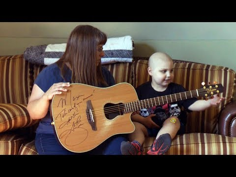 Garth Brooks stops concert to gift guitar to cancer survivor