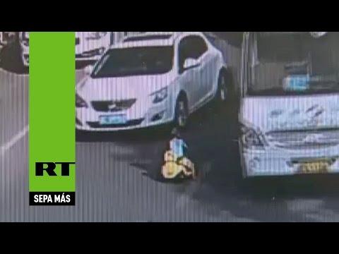 Bimbo (cinese) in strada con l'auto giocattolo, salvato dal vigile urbano.