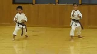 Мальчик и девочка (6 и 7 лет) сдают экзамен на черный пояс по карате