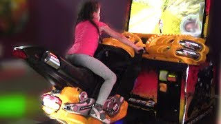 Kids play in an indoor playground and ride on bikes and cars