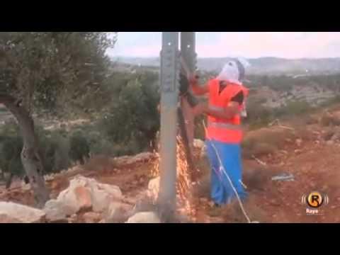 Hamas members taking down electric pole