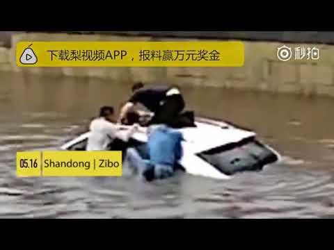 Good Samaritans rescue a woman trapped inside a submerged SUV in flood waters