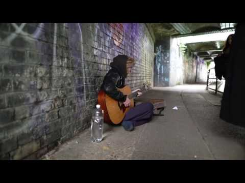A busker playing and singing roots rock reggae song by Bob Marley - reggae music