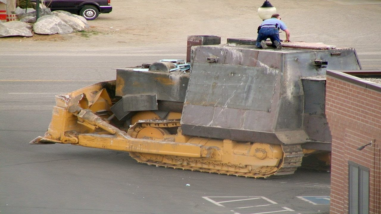 Sheriff's Deputy Glenn Trainor on top of the bulldozer looking to find a way to disable it or strike at Marvin Heemeyer.