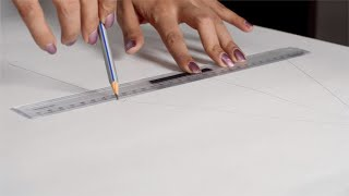 Close shot of women hands drawing straight line with a ruler and pencil